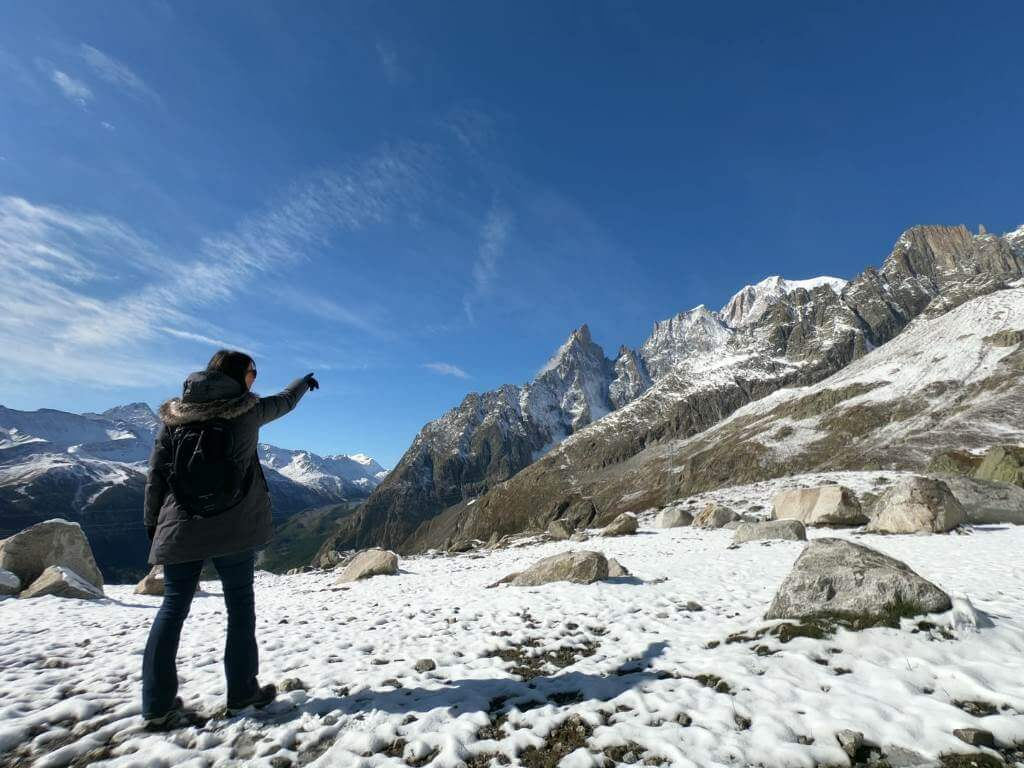 Girl standing on snow pointing to a mountain peak with blue skies in the background