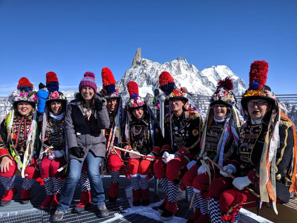 A group of Le Beuffon, people in traditional Courmayeur outfits, sitting with mountain views in the background
