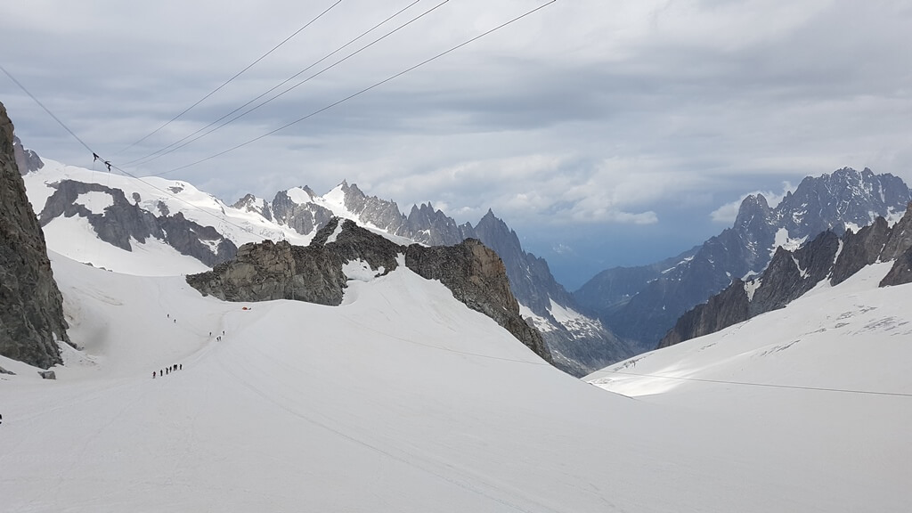 mountainous snowy views from the Punta Helbronner platform on the Skyway Monte Bianco Cable Car.  Climbers in the distance on the snow